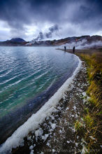 People walk along the shore of Lake Myvatn in northern Iceland in Autumn