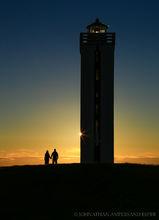 Couple walks around Kalfshamarsvik Lighthouse in northern Iceland at sunset
