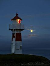Torshavin harbour lighthouse and full rising moon above sea fog