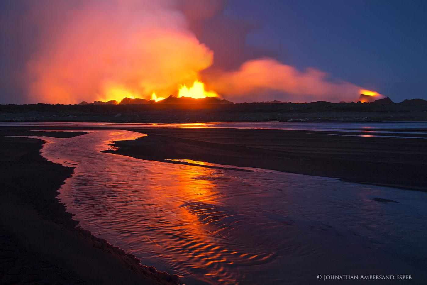 Holuhraun eruption red glow reflection in an intermittent stream, after sunset