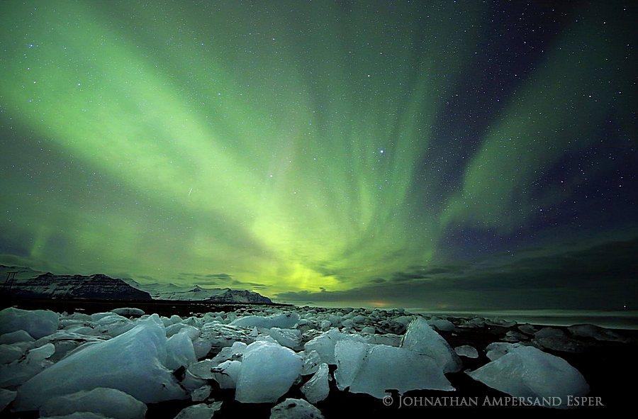 Aurora borealis display over icebergs on the black sand beach Breiðarmerkursandur, Iceland